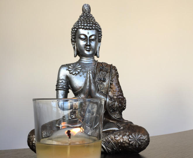 Buddha sitting by candel